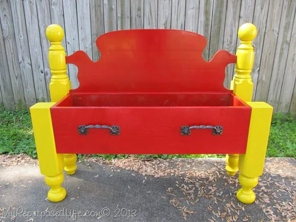 repurposed headboard into a red flower bed