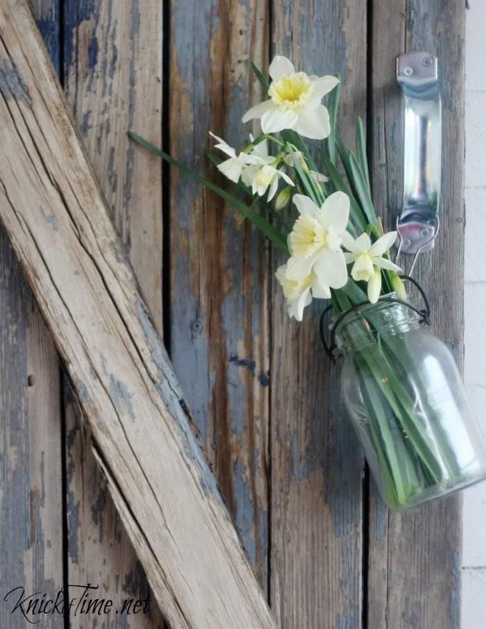 flowers in mason jar on barn gate