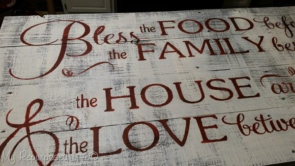 reveal of rustic sign with wax stenciled letters