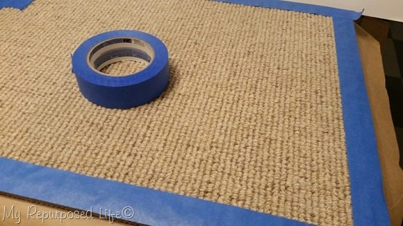 apply painters tape around the perimeter of a cheap rug
