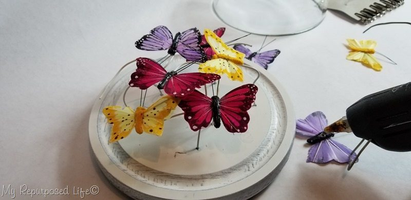secure butterflies to wire with hot glue