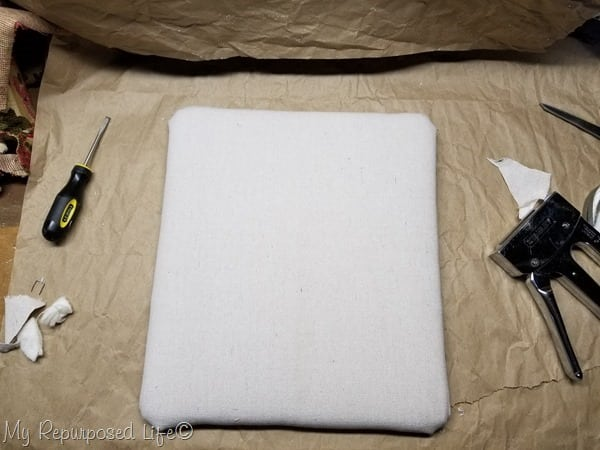 upholstered footstool top with drop cloth