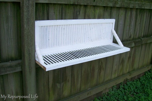 white chippy shutter shelf made with bi-fold doors hanging on fence