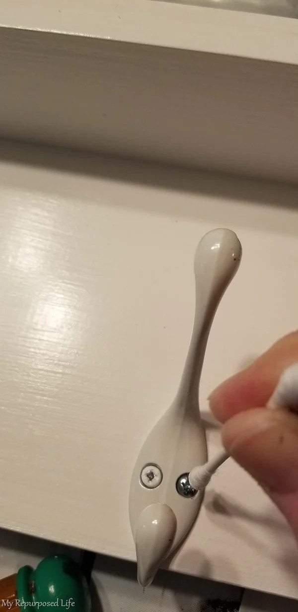 dab white paint on screw head with cotton swab