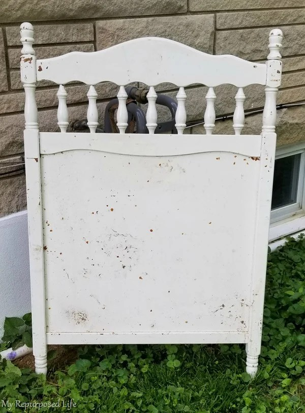vintage crib repurposed as a faux garden gate gas meter cover