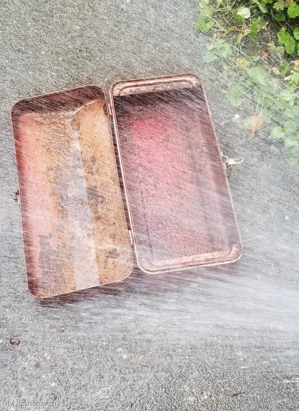 washing vintage toolbox with hose