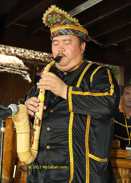 Kadazan man plays bamboo saxophone