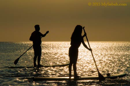 stand up paddle boarding under sunset