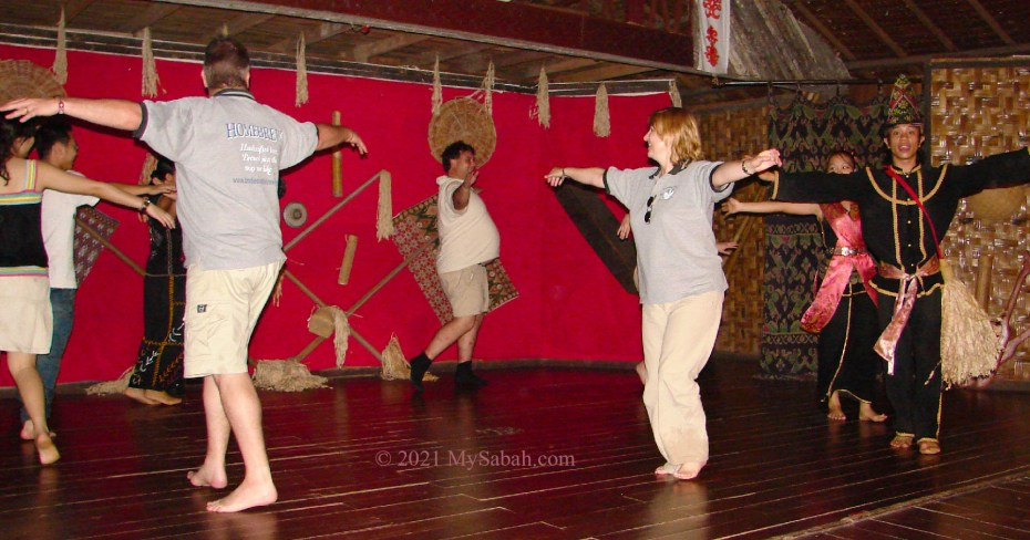 Tourists trying Sumazau dance in cultural village