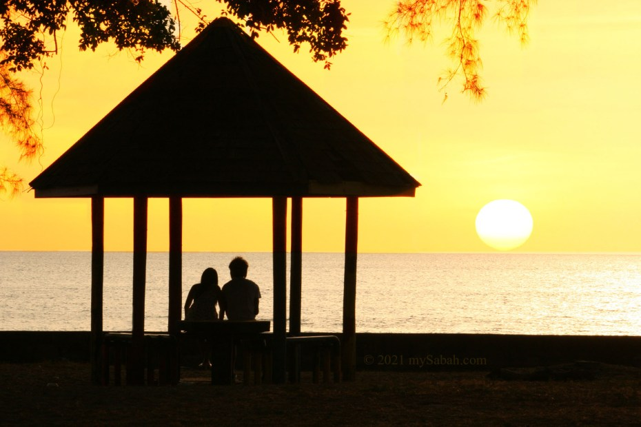 Couples looking at sunset of Tanjung Aru Beach from a gazebo