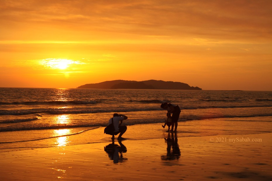 A family with child at Tanjung Aru Beach during sunset