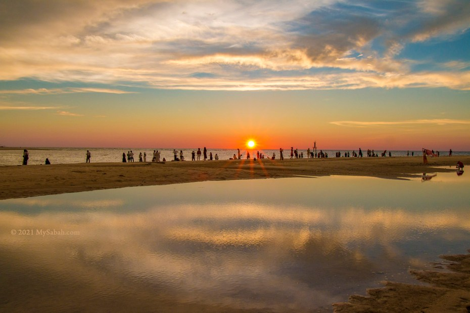 Tourists watching sunset at Dalit Beach, where Mengkabong River meets the sea
