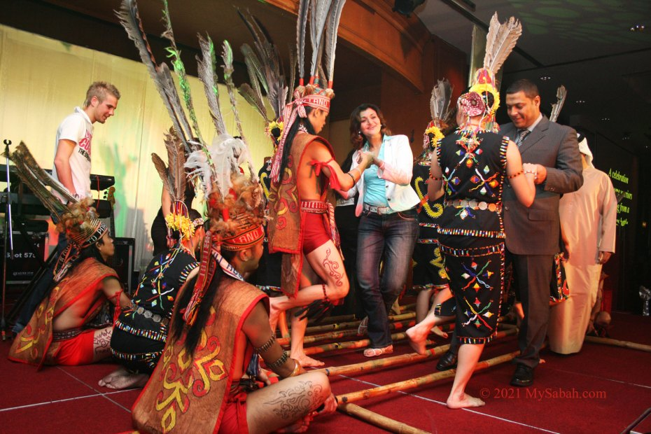 Tourists trying bamboo dance