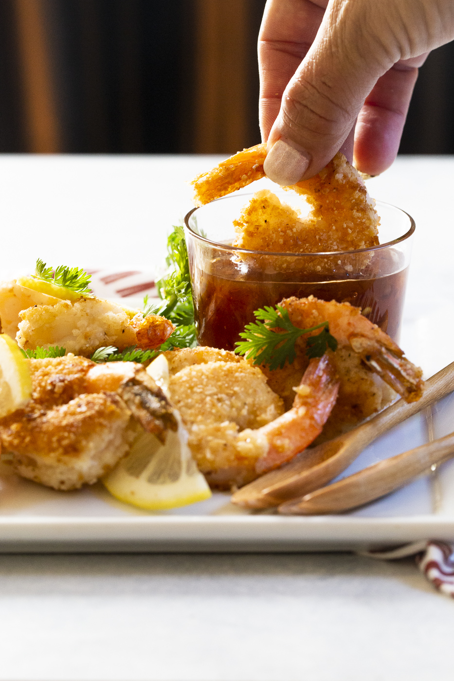 coconut shrimp being dipped in a spicy apricot sauce.