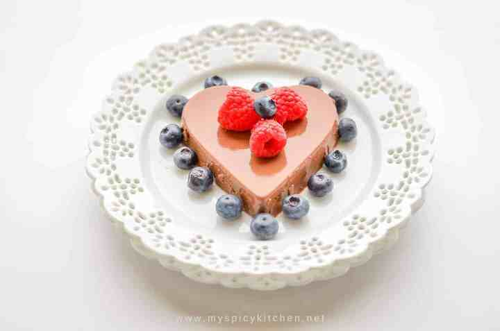 A plate of heart shaped mocha panna cotta garnished with raspberries and blueberries styled on a white background