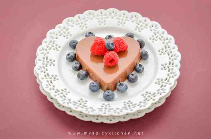 A plate of heart shaped mocha panna cotta garnished with raspberries and blueberries