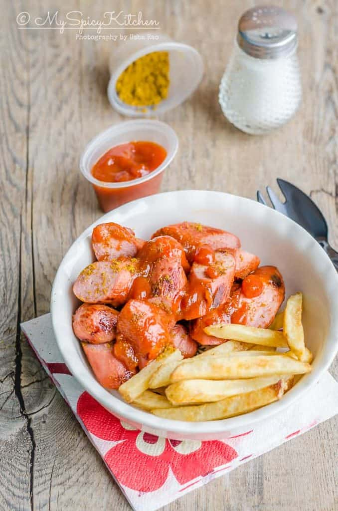 Currywurst, German street food and national dish.  Grilled pork sausage is served with curry flavored ketchup or tomato sauce.