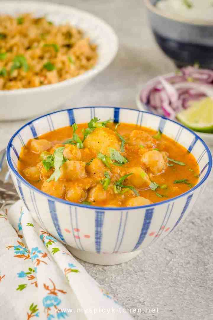 A bowl of South Indian chickpeas curry in the forefront.  Bowl of spinach rice yogurt and onion salad in the background