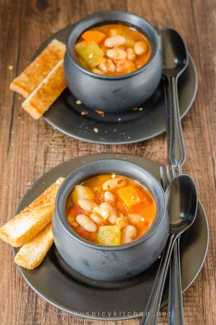 Two bowls of vegetable cannellini bean soup, each plated in a plate with some bread on the side