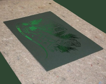 Green reflective foil print of an iguana in front of cinder blocks, and printed on dark green paper