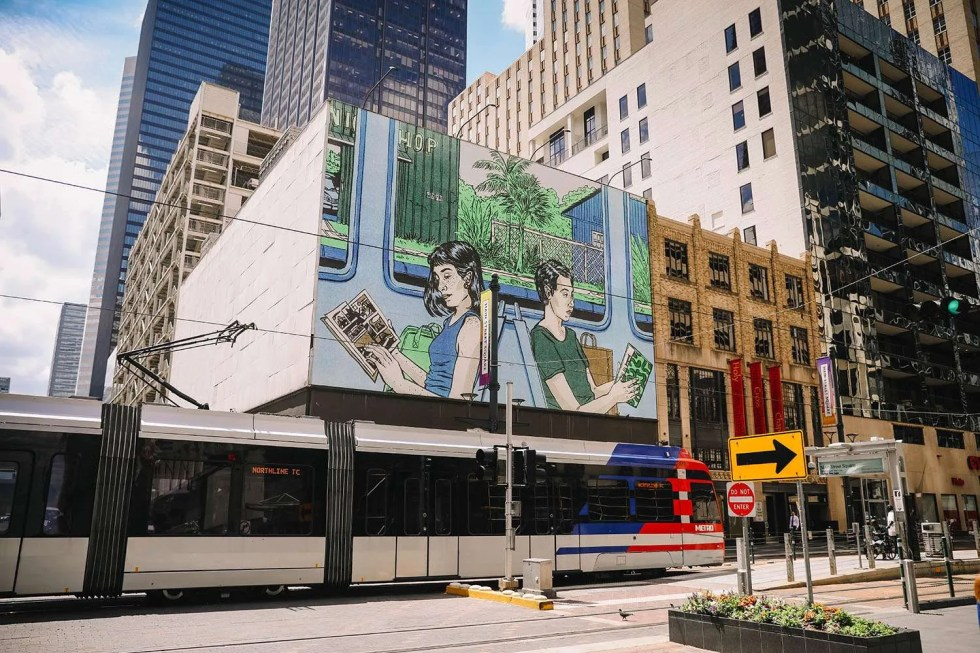 Photograph of main street market mural by Sarah Welch installed in downtown Houston, featuring two women reading on the metro light rail