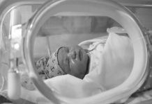 A newborn baby in an incubator