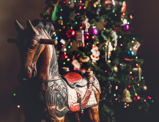 Wooden rocking horse in front of a decorated Christmas Tree