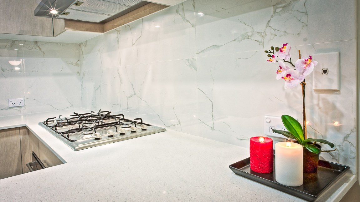 white kitchen with led lighting and led candles to the right of the picture