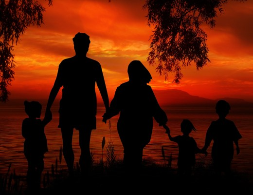 A family of five holding hands stood on a bank over looking a lake at sunset