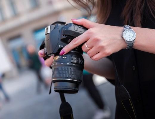 A woman photographer holding a Nikon dslr camera
