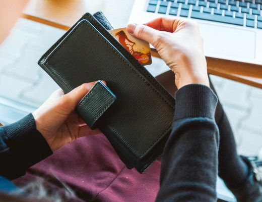 A woman sat in front of a computer, reaching for her credit card in her purse