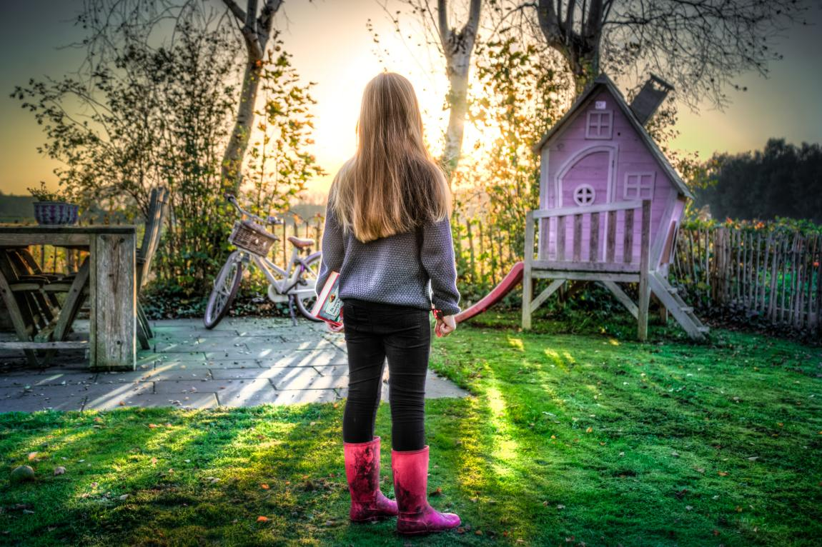 a little girl in a garden near a pink Wendy house and bicycle