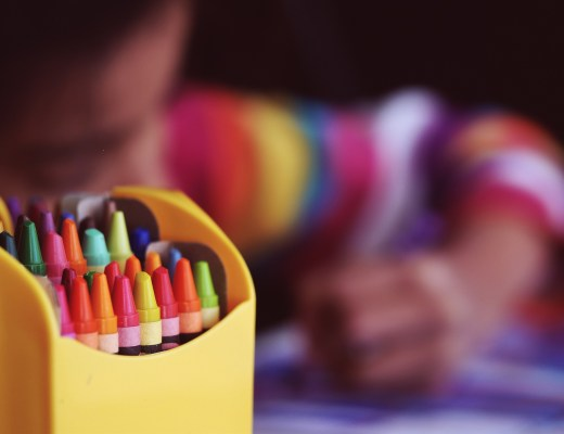 A box of crayons sat in front of a child colouring in