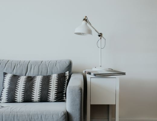 A light grey sofa up against a white wall. next to the sofa is a small white table with a white lamp and a book on it.