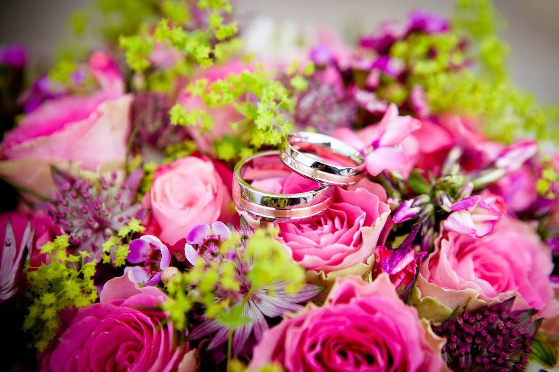 A brightly coloured wedding bouquet with wedding rings sat on top