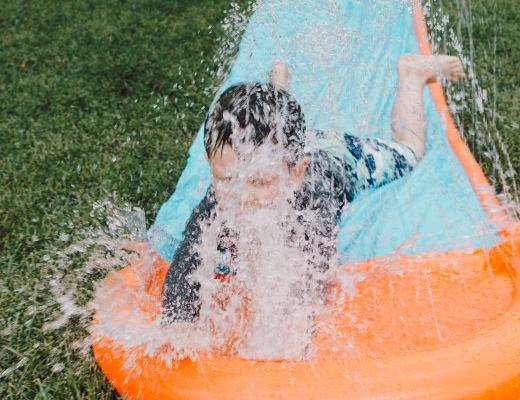 boy coming down a water slide in a garden