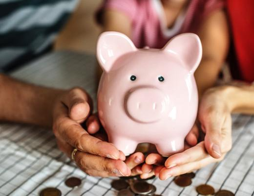 two pairs of hands holding a pink piggy bank with lots of money around it