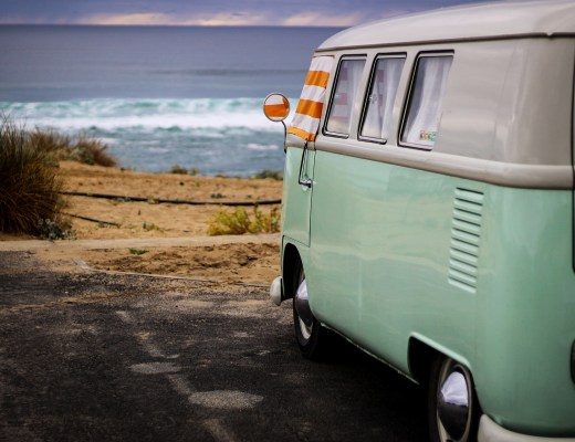 Green VW campervan parked near the beach