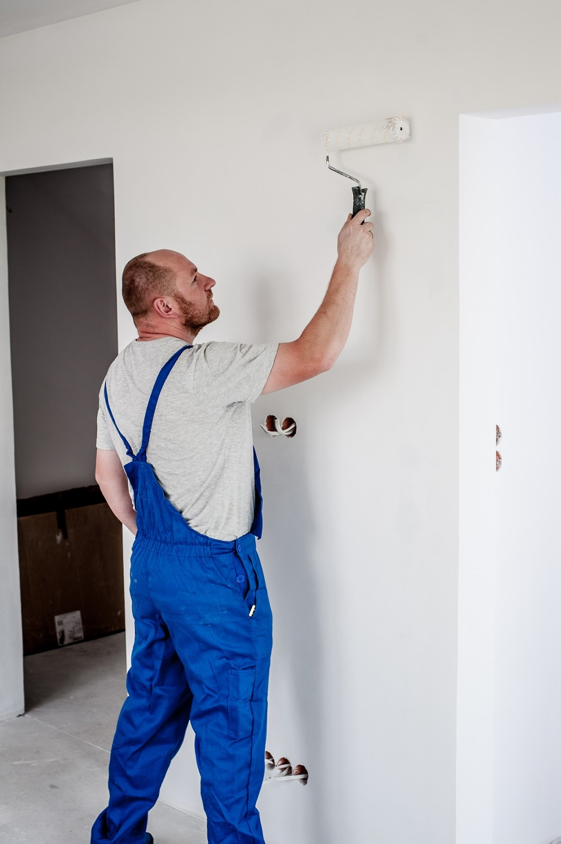 a man in blue overalls painting a wall white inside a house