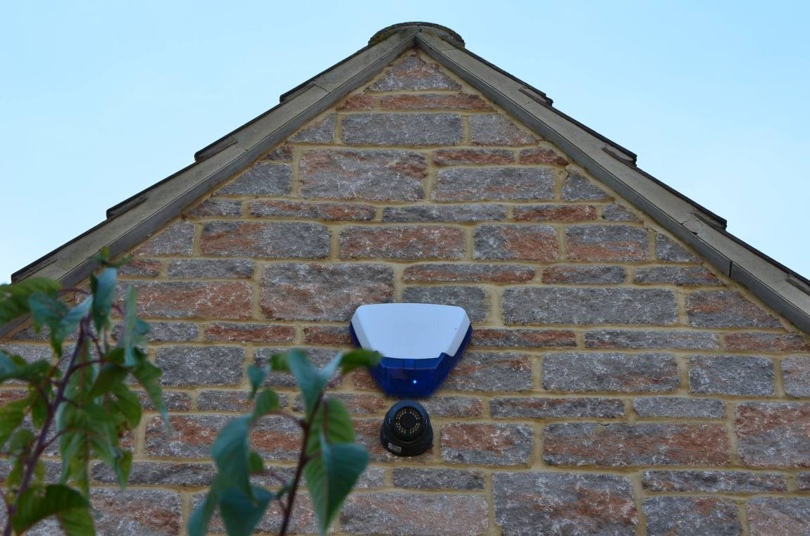a security camera and a burglar alarm on the side of a house