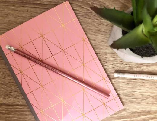 a pink pencil and pink notebook sat on a desk in an office