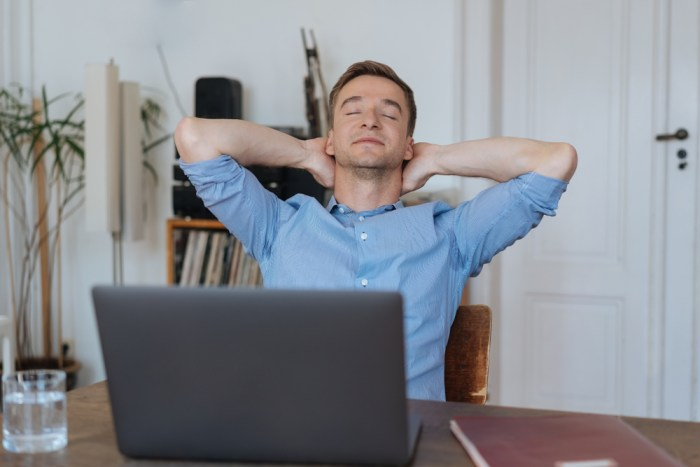A man sat at his computer looking contented.