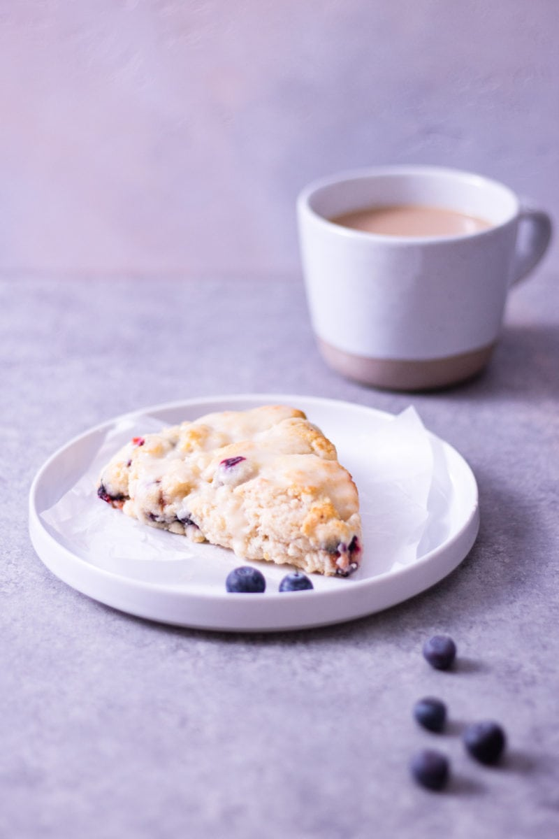 Angled view of a lemon blueberry scone on a plate surrounded by scattered fresh blueberries with a mug of coffee in the background on a light grey surface.
