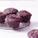 Straight on shot of Double Chocolate Chip Muffins on a wire rack on a white surface.
