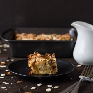 Straight on shot of a slice of Panettone Bread Pudding with Brandy Sauce on a plate next to forks, a jug of sauce and the rest of the bread pudding in the background on a dark wood surface.