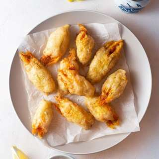Fried Squash Blossoms on parchment on a plate surrounded by lemon wedges and a beer can.