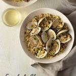Overhead shot of two light, rustic bowls of fregola pasta with clams surrounded by a glass of white wine and a neutral colored towel on a light, cream colored, textured plaster surface.