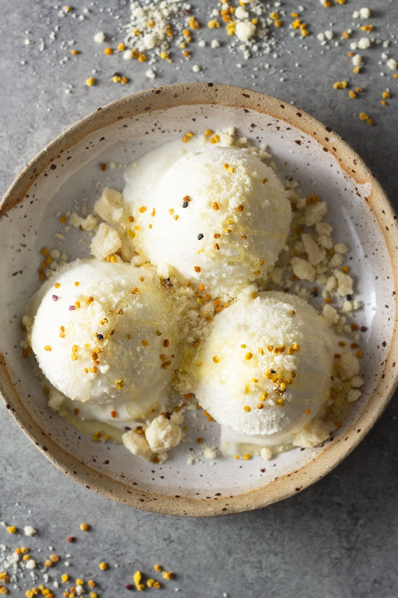 Overhead shot of a rustic ceramic bowl filled with milk ice cream, milk powder crumble, bee pollen and acacia honey on a light grey, textured surface.