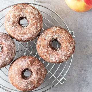Overhead shot of Apple Cider Donuts with Cinnamon Sugar on a round, wire rack on a light grey, textured surface surrounded by a glass of apple cider and an apple.