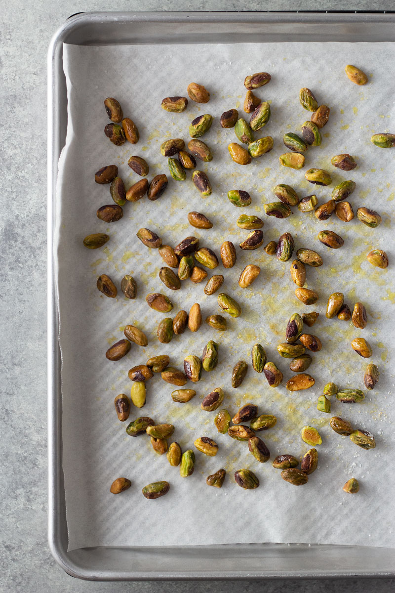 Overhead shot of buttery, salted pistachios on a parchment lined sheet tray after toasting.